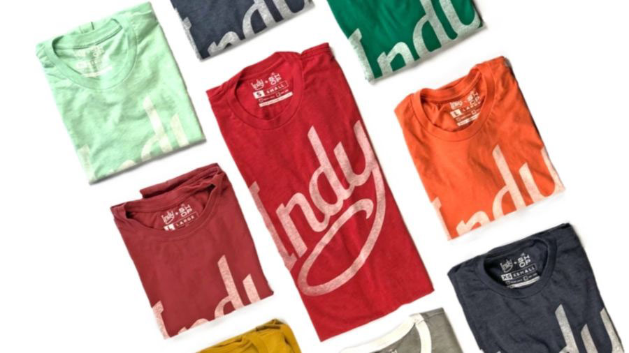 multiple Indy-branded tees folded next to each other. Red, Green, Blue, Grey, Orange, Mint