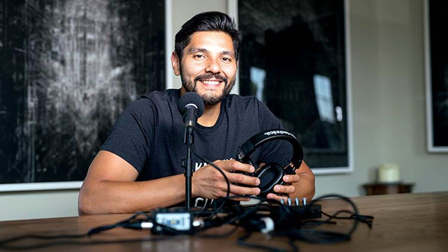 Fabian Rodriguez - sitting at a table in a recording studio smiling with headphones in his hands