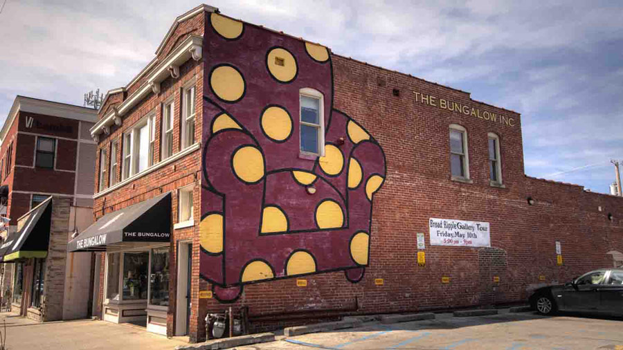 Red armchair with yellow polka dots on the side of a building in Broad Ripple