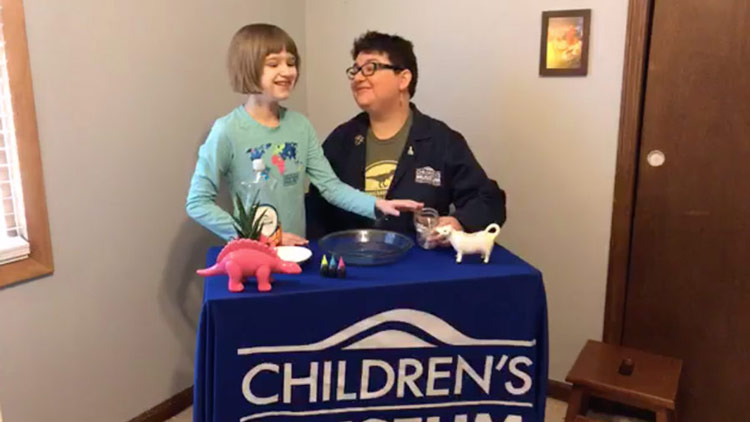 "Mother and Daughter Working on science experiments at a table with banner reading ""The Children's Museum of Indianapolis"""