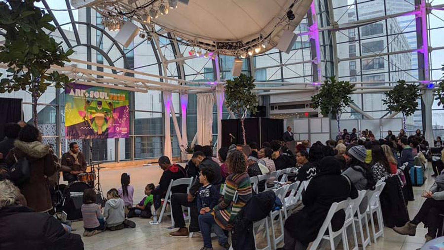 a gathering of people in the Artsgarden, a glass dome room
