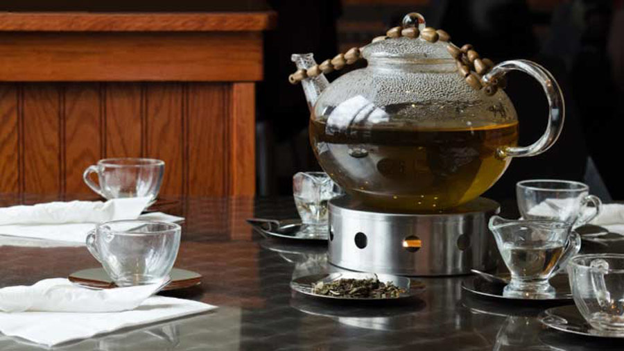 A grand teapot filled with black tea, and six teacups sitting around it on an oak table