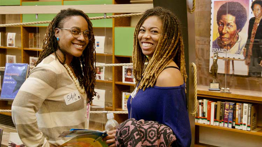 Two Black Women smiling with bookshelves behind them