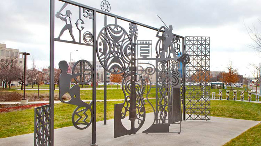 A iron sculpture showing people performing various activities - biking, playing baseball, playing the violin,