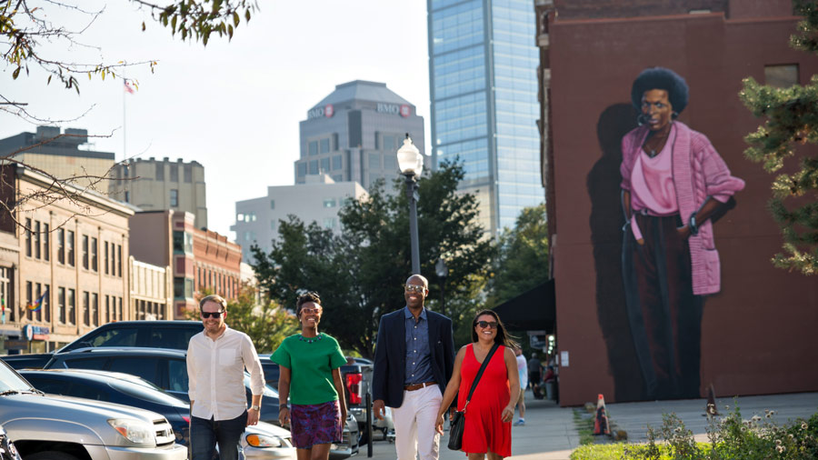 A group of people walking, smiling on the sidewalk. Behind them, a larger-than-life mural of poet Mari Evans looks over the street