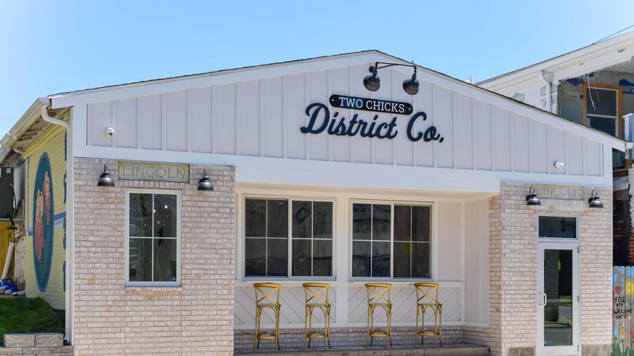 """the exterior of Two Chicks District Co., sign on the building says """"Two Chicks District Co."""""""