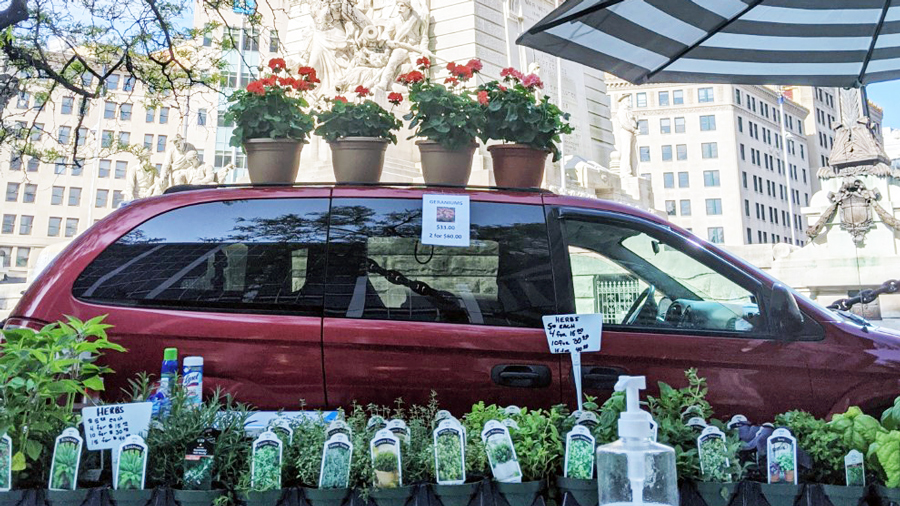 a red minivan with flowers on top and plants being sold in front of the van. Images is taken in downtown indianapolis by the Soldiers & Sailors Monument.
