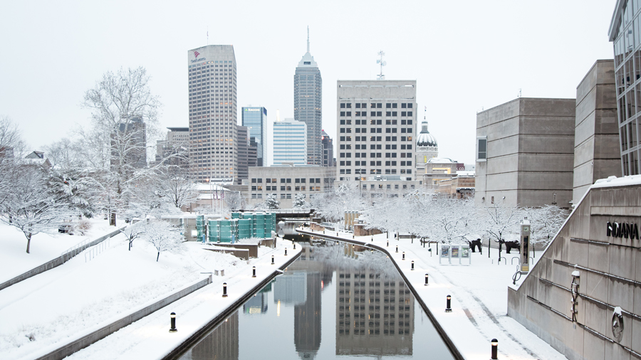 Snow on the Central Canal, with the skyline of Indianapolis visible.