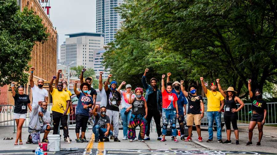 A group of artists stand over a #BlackLivesMatter mural. Their hands are held in the air in fists.