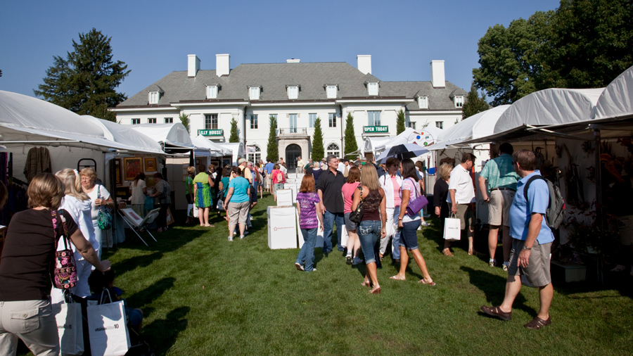A group of people shopping at the Penrod Arts Fair. The Lilly House, a white house on Newfield's campus, is in the background.