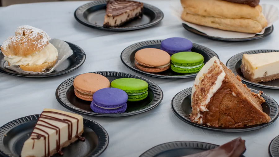 Small plates with French pastries. Pies, macarons, and cakes.