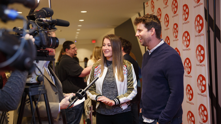 Two people standing in front of cameras and microphones, being interviewed on the red carpet for Heartland INternational Film Festival