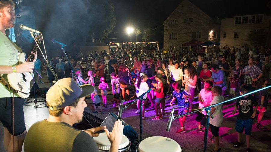 A band playing guitars, drums, and singing to a crowd of people