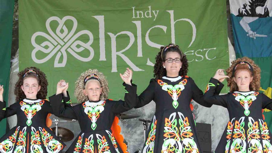 "Four girls dancing in Irish Costumes. Sign behind them reads ""Irish Fest"""