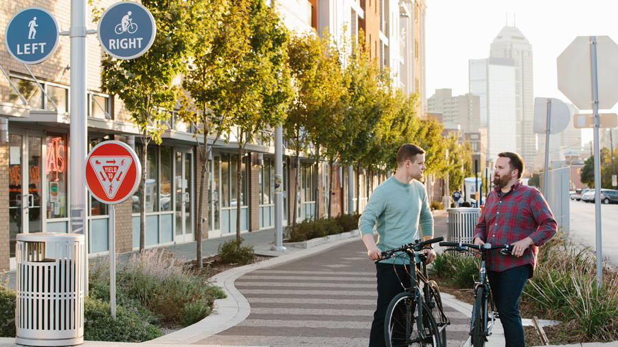 Two people standing next to bikes along the Indianapolis Cultural Trail; the city skyline is in the background.