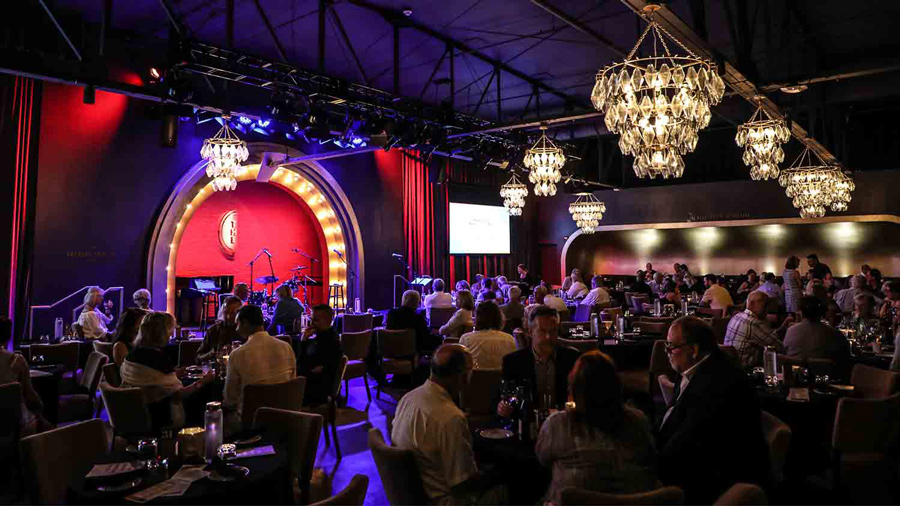 The Cabaret Theater interior. Multiple chairs and tables are gathered to look at a stage. Chandeliers hang overhead
