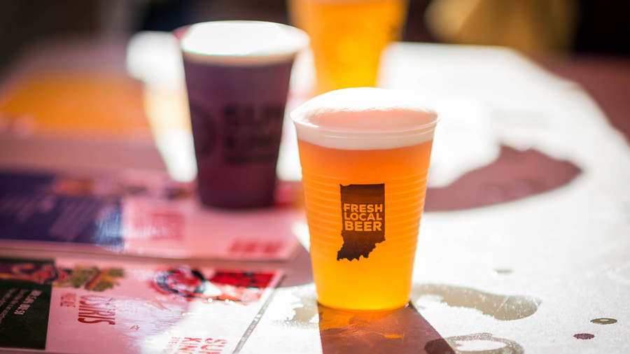 """Two plastic cups of beer, one reads """"Fresh Local Beer"""" on a graphic of Indiana"""